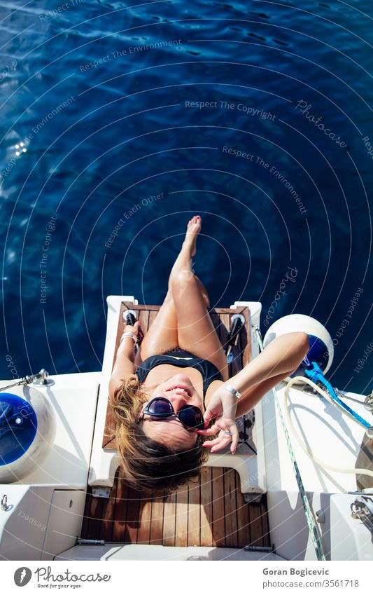 Young woman relaxing on the yacht on sea at sunny day adult alone attractive beautiful blue board boat calm caucasian cruise cruising deck female happy holiday