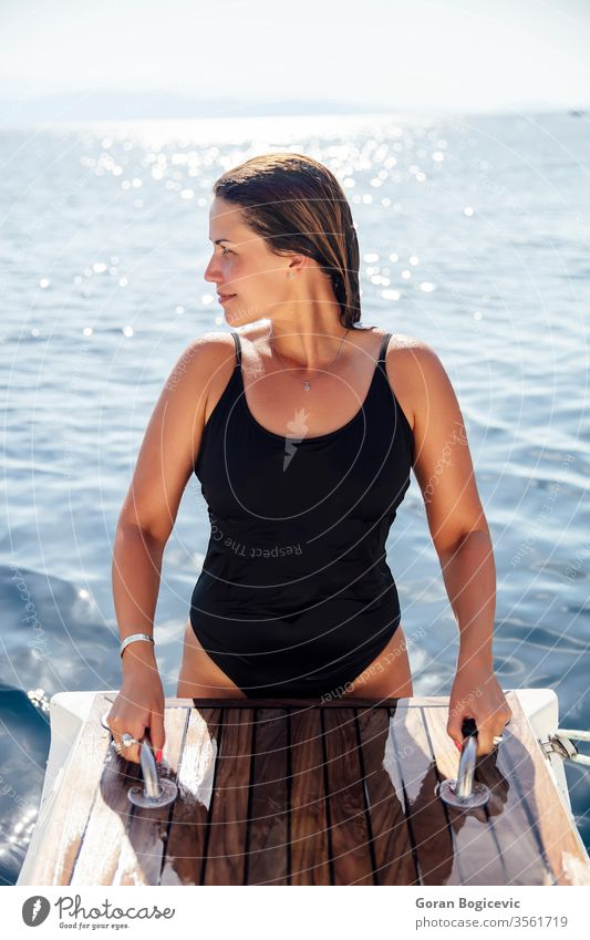 Young woman get on the yacht on sea at sunny day adult alone attractive beautiful blue board boat calm caucasian cruise cruising deck female happy holiday