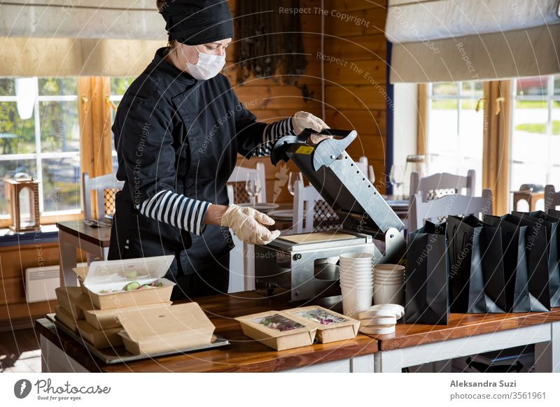 Restaurant worker wearing protective mask and gloves packing food boxed take away. Food delivery services and Online contactless food shopping. business buy