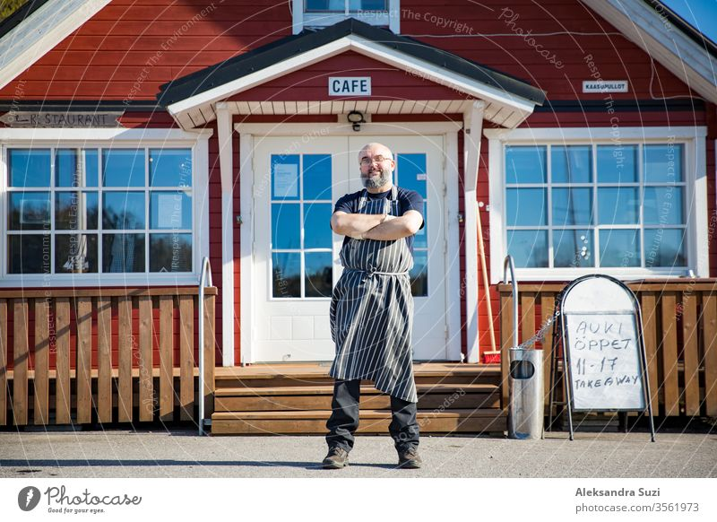 Portrait of a confident mature man with beard, restaurant employee wearing aprons standing in front of the restaurant. Small business concept. arms barista