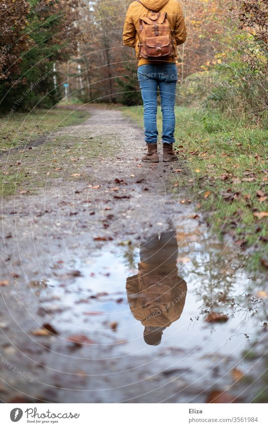 Man stands on a path in the forest and is reflected in a puddle Forest Puddle reflection To go for a walk Rain slush Autumn Trip hike Hiking Reflection Nature