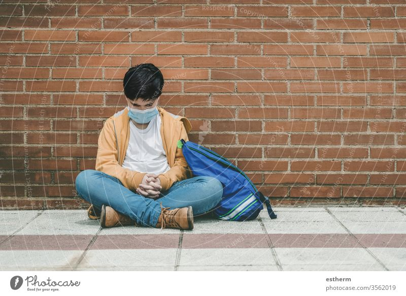 sad kid with medical mask and backpack coronavirus child epidemic covid-19 school student pandemic quarantine city schoolboy sadness preoccupation dejected