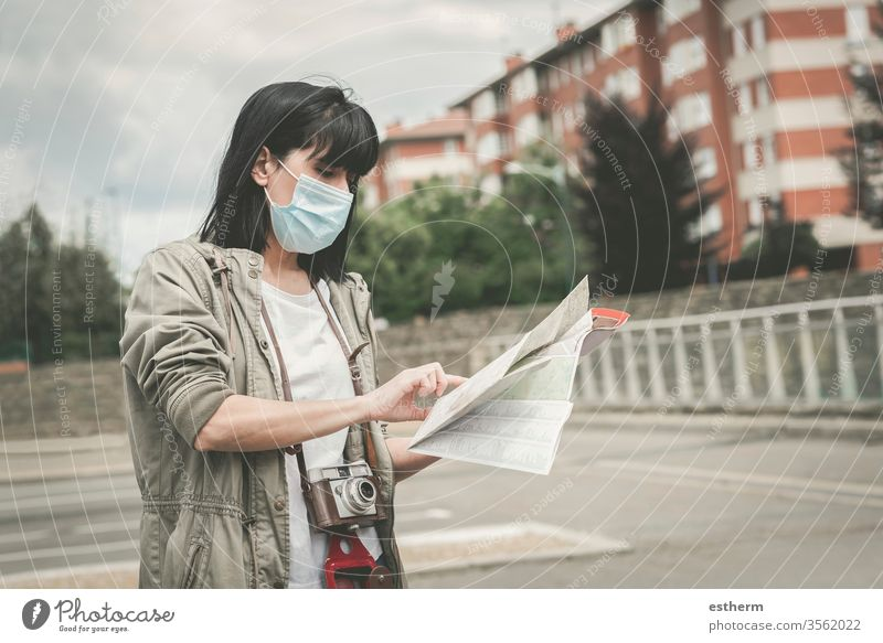 woman wearing medical mask with a camera look at a map of the city coronavirus young woman epidemic traveler traveling tourist tourism holidays pandemic