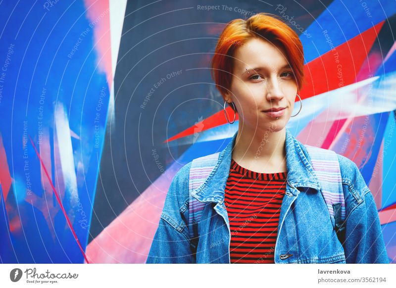 Young adult white woman in jeans jacket with died red hair, lifestyle portrait with selective focus attractive casual caucasian dyed fashion female graffiti
