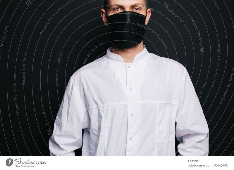 young doctor with short hair in a medical gown uses a black protective mask. male laboratory assistant in a protective suit to work with patients with coronavirus infection during the pandemic.