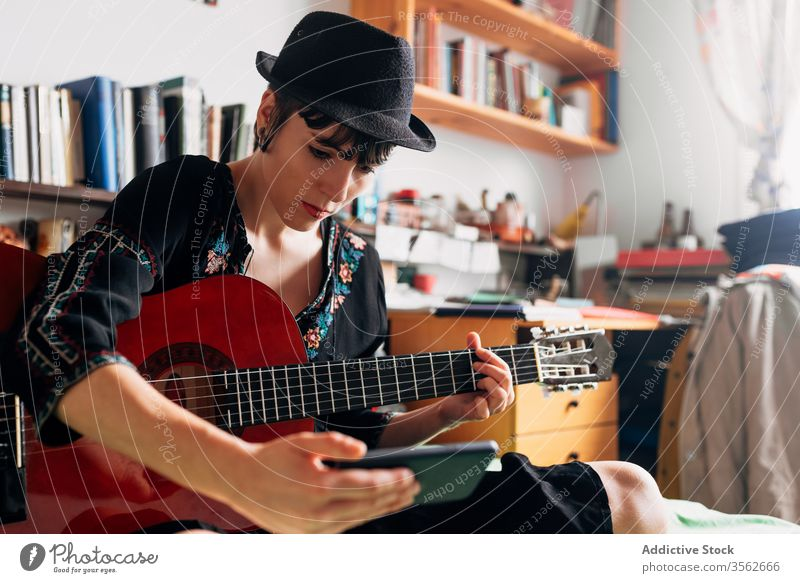 Woman with guitar looking at smartphone at home woman browsing acoustic trendy message using cellphone music female weekend style wear hat bed sit relax gadget