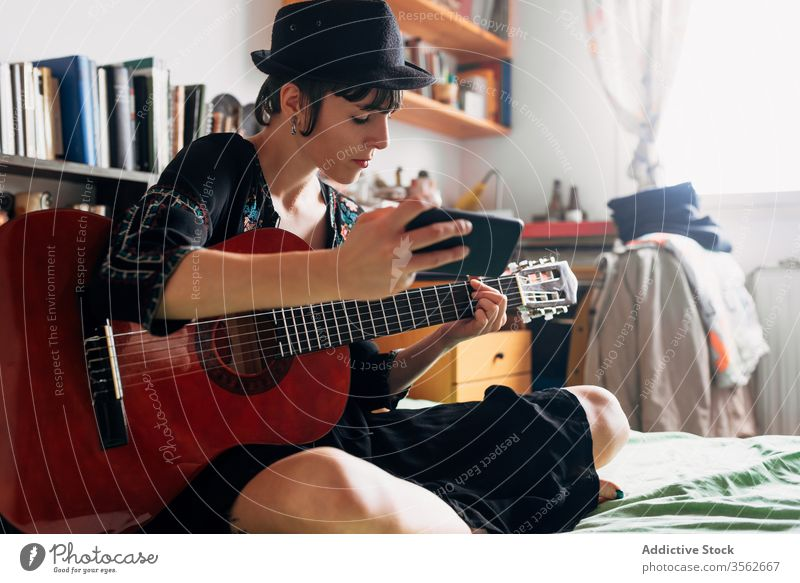 Woman with guitar and smartphone at home woman browsing acoustic trendy message using cellphone music female weekend style wear hat bed sit relax gadget device