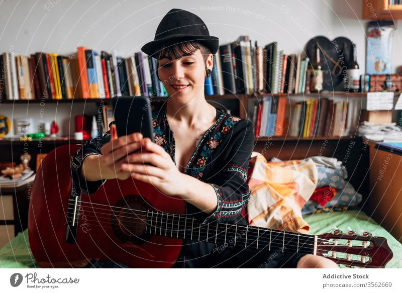 Cheerful woman with guitar browsing smartphone at home acoustic trendy message using cellphone music female weekend style wear hat bed sit relax gadget device