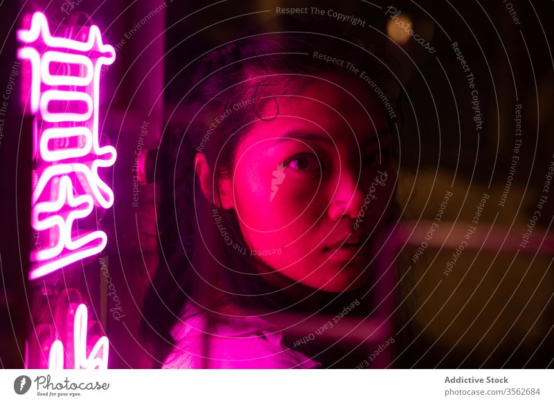 Young Asian woman standing near signboard at night neon mysterious dark ethnic asian pink illuminate chinese hieroglyph color emotionless thoughtful alone