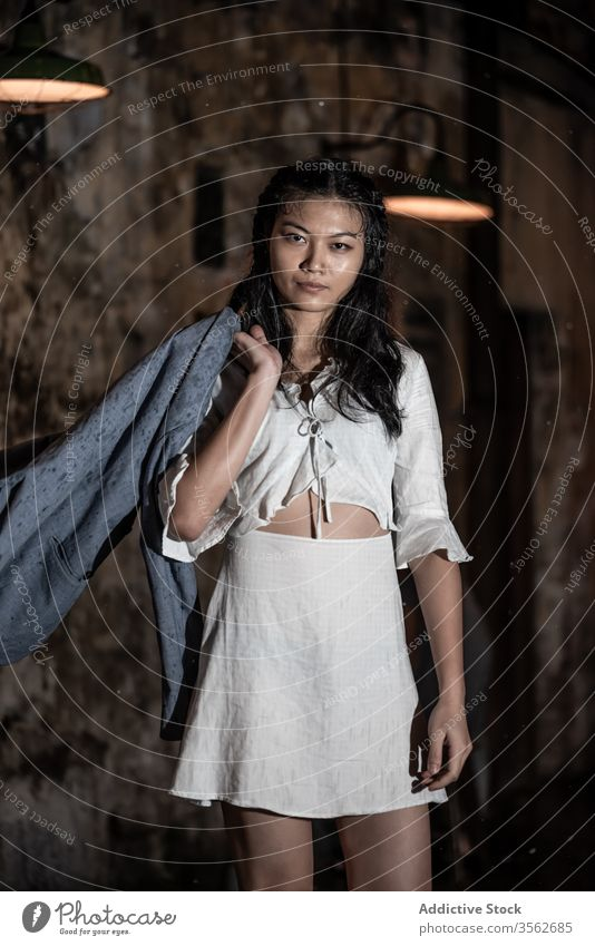 Serious Asian woman in white wear standing near brown wall town stroll emotionless white dress thoughtful style skirt appearance slim lamp confident feminine