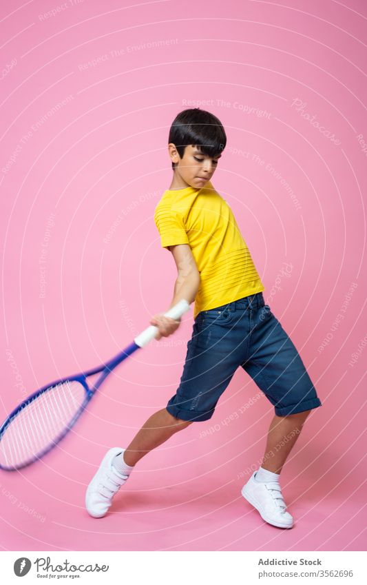Focused little boy playing tennis hit ball racket training colorful bright kid child sport fun game activity equipment competition hobby recreation court match