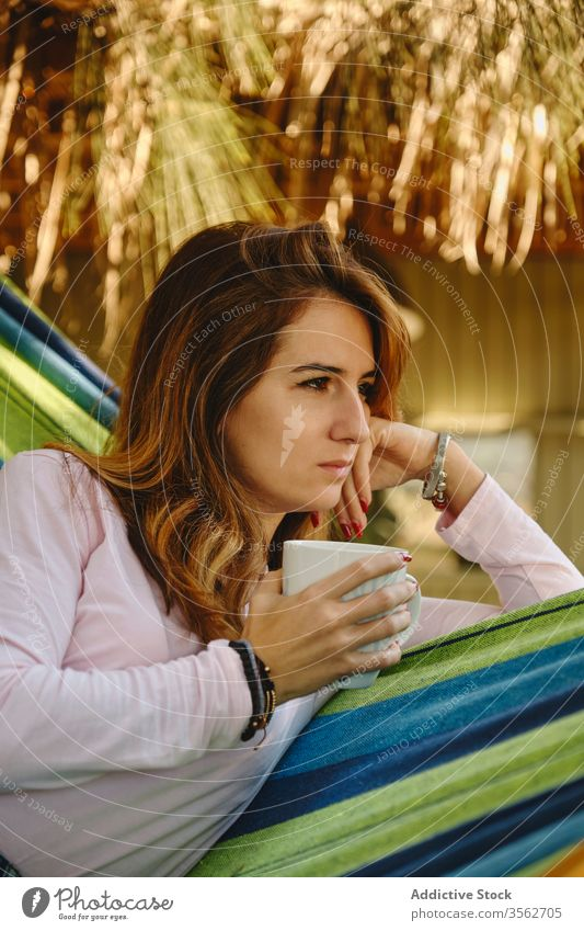 Relaxed woman with cup of coffee in hammock relax hot drink calm lying barefoot courtyard enjoy female summer holiday vacation weekend mug casual outfit