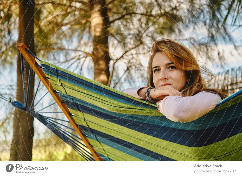 Relaxed woman in hammock in the sunset relax calm lying courtyard enjoy female summer holiday vacation weekend casual outfit lady rest peaceful tranquil young