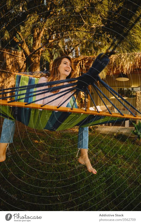 Relaxed woman in hammock in the sunset relax calm smiling happy lying courtyard enjoy female summer holiday vacation weekend casual outfit lady rest peaceful