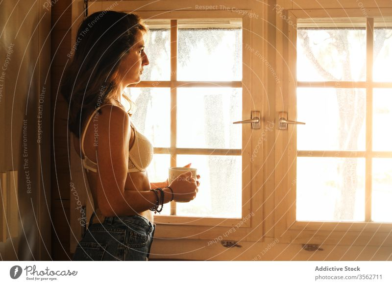 Relaxed woman with coffee near window in morning relax enjoy weekend cabin serene beverage female jeans bra cup hot drink stand rest young cottage wooden lady