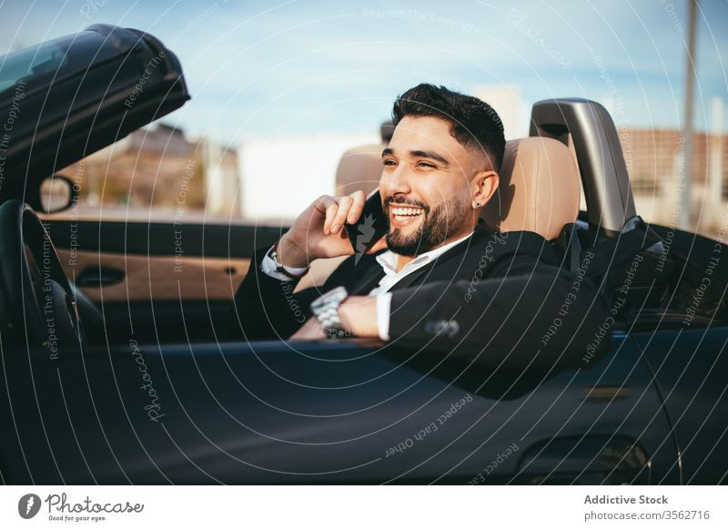 Attractive businessman with convertible car, calling by mobile automobile person people young driver traffic vehicle fashion phone talking success cruise