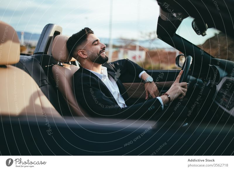 Attractive businessman with convertible car automobile person people young driver traffic vehicle screen assistance fashion cruise purchase suit road technology