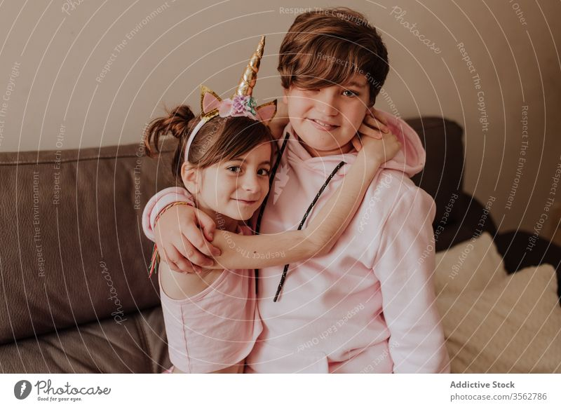 Siblings hugging each other near couch sibling home love sofa together sister brother living room cozy teen kid child cute boy girl lifestyle friend relax joy