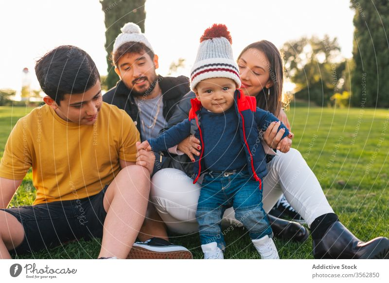 Happy family with kids resting on green meadow together park love happy grass portrait relationship positive cheerful autumn young toddler child parent nature