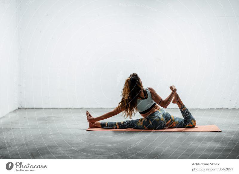 Slim woman practicing yoga on mat practice front split hanumanasana pose slim female flexible sit floor sportswear active wear fit healthy meditate harmony lady