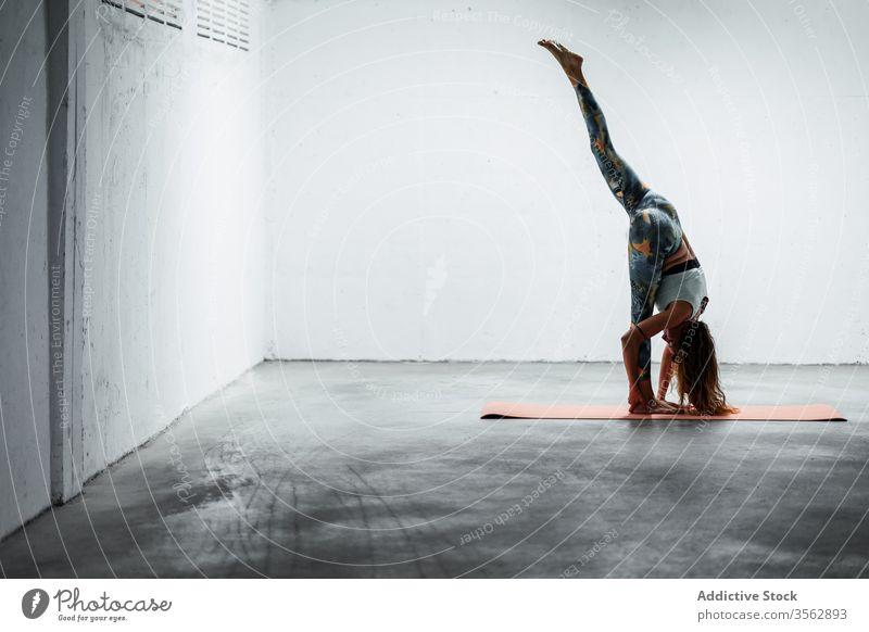Tranquil woman doing standing split on mat yoga practice flexible balance tranquil harmony female calm pose slender asana slim floor sportswear active wear lady