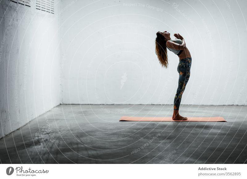 Slender woman doing yoga in Mountain pose with raised arm balance practice calm standing backbend slender asana female slim mat flexible floor sportswear