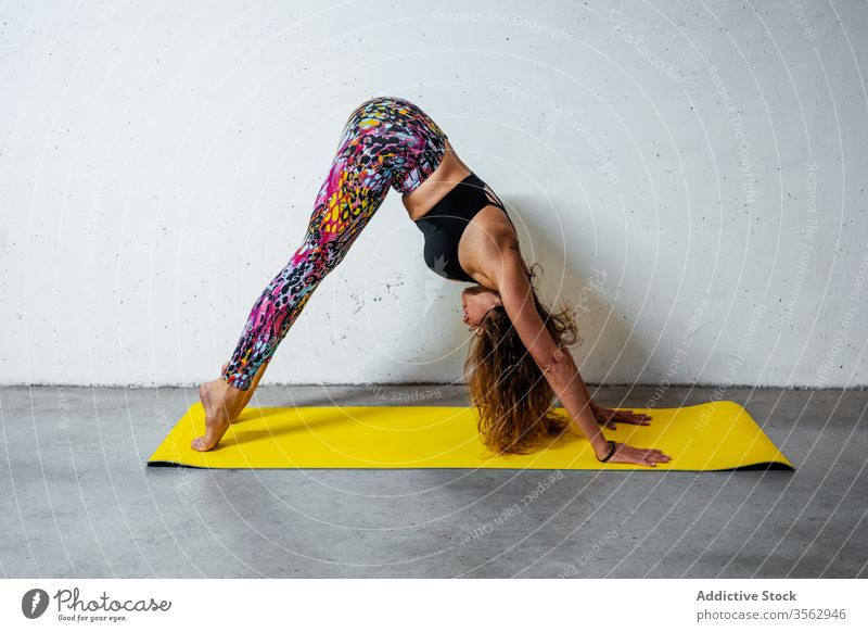 Woman practicing yoga on mat woman pose practice downward facing dog adho mukha svanasana posture position balance flexible concrete activity wall modern