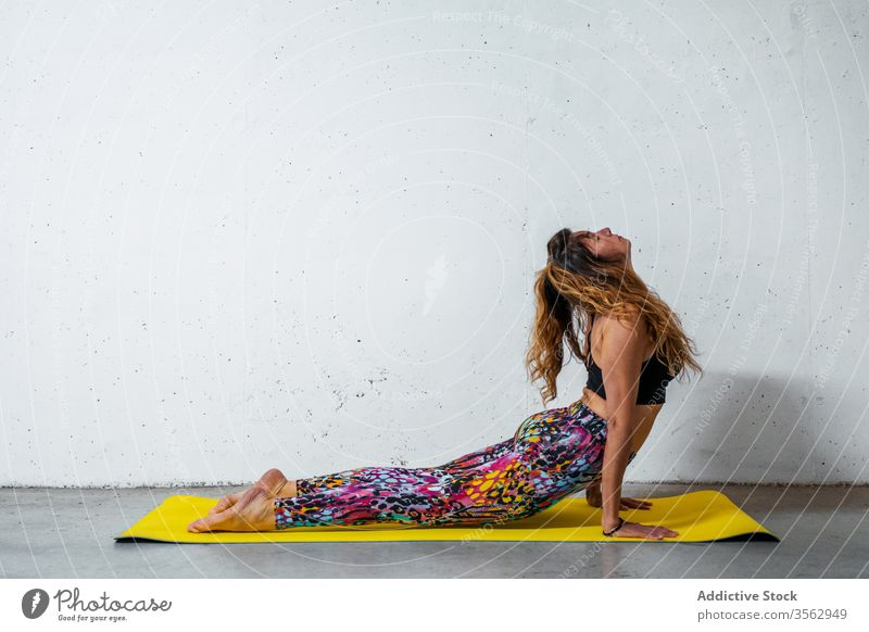 Woman practicing yoga on mat woman practice upward facing dog pose bhujangasana posture position balance eyes closed flexible concrete activity wall modern