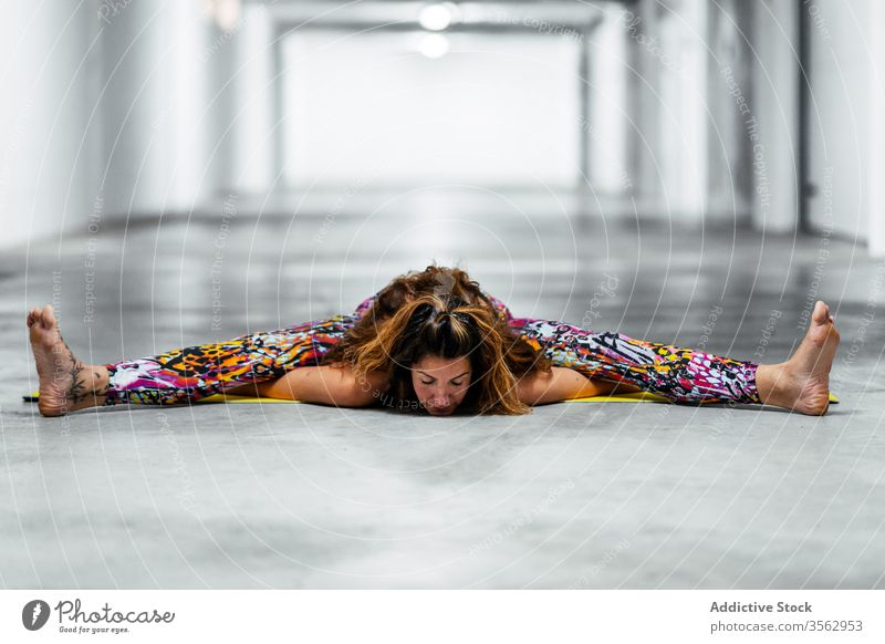 Young woman practicing yoga in seated forward bend position practice asana garage pose upavistha konasana advanced stretch split angle flexible young female