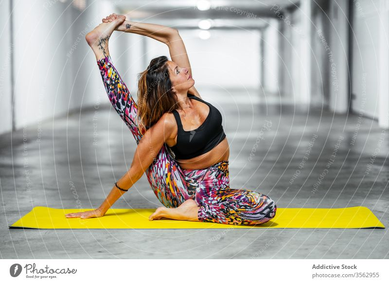Woman stretching body in yoga pose woman practice compass asana garage position parivrita surya yantrasana flexible advanced challenge balance posture young