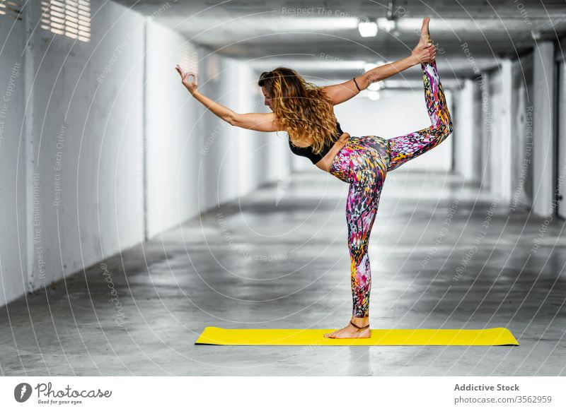 Experienced woman practicing advanced yoga asana practice lord of the dance pose garage position flexible natarajasana challenge balance posture young female