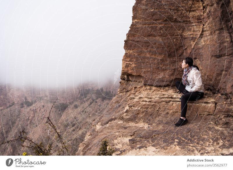 Ethnic traveler sitting on rock woman mountain fog explore ethnic rough nature female casual cliff journey asian adventure landscape trip freedom tourism lady