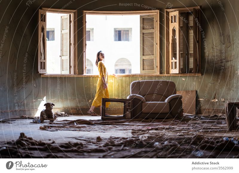 Woman standing in living room of abandoned house woman window uninhabited old shabby messy apartment residential young ethnic female saudi arabia jeddah asian