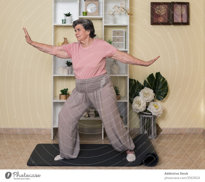 Positive senior woman practicing yoga at home pose balance calm mat activewear practice exercise vitality serene tranquil stretch recovery recreation elderly