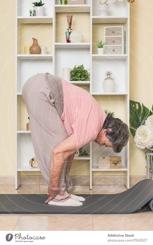 Flexible senior woman doing stretching exercise on mat at home flexible bend forward stand yoga elderly practice asana peaceful lifestyle serene meditate care