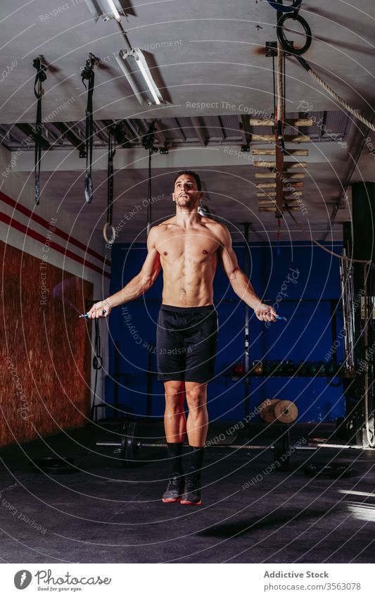 Fit sportsman exercising with jumping rope exercise skip fit active endurance training naked torso male muscular workout strong gym muscle confident focus