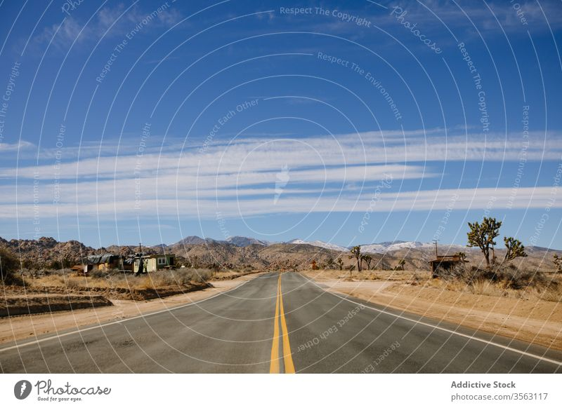 Empty highway on rocky countryside road road trip route desert asphalt sand dry heat mountain picturesque nature valley calm range freedom usa sky california