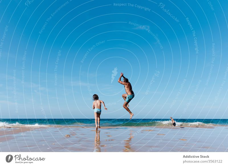 Father and kid having fun on beach father sea jump together happy vacation holiday man water summer run sand ocean coast shore child joy nature carefree