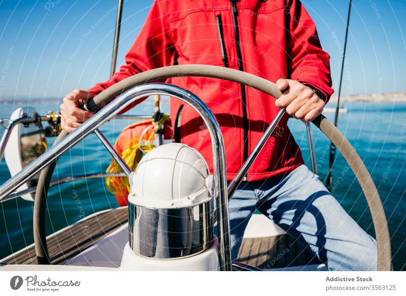 Anonymous man sailing on boat steering wheel helm sea adventure summer activity modern vessel travel transport water trip journey lifestyle ocean male ship