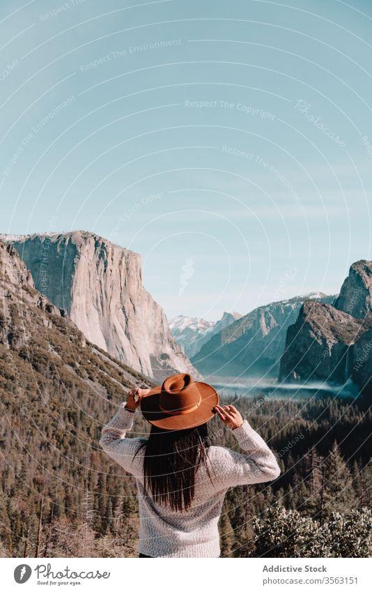 Traveler enjoying majestic mountain landscape woman travel cliff rock national yosemite park forest hill female hat picturesque scenery granite sunny blue sky