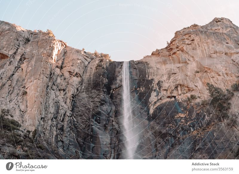 Rough rocky cliff with waterfall mountain rough power stream yosemite national park usa sky nature landscape stone travel tourism california united states