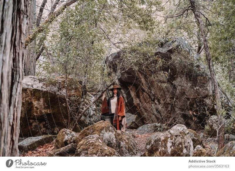 Young woman standing near large stones in forest rock boulder travel trendy style tree landscape yosemite park boho rustic united states mountain national