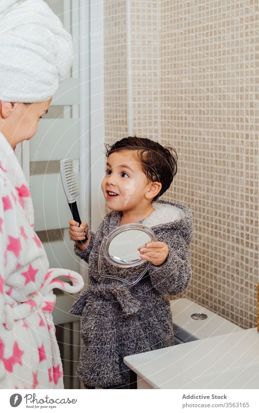 Little boy brushing hair in bathroom comb mother child adorable wet hair mirror kid childhood parenthood mom son motherhood bright together relationship toddler