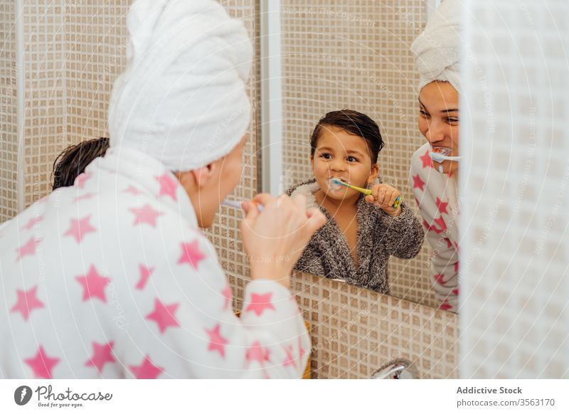 Cheerful son and mother with toothbrush in bathroom teeth boy bathrobe oral hygiene smile little child mom parenthood healthy mirror kid wet hair dental care