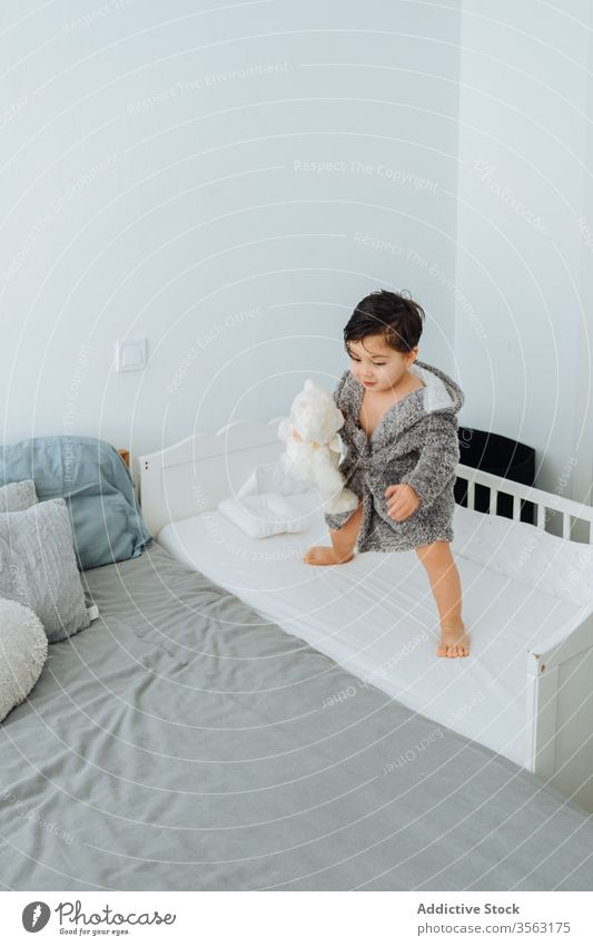 Content little boy in bathrobe playing with teddy bear child having fun weekend crib bedroom cute kid game content playful toy soft plush childhood adorable