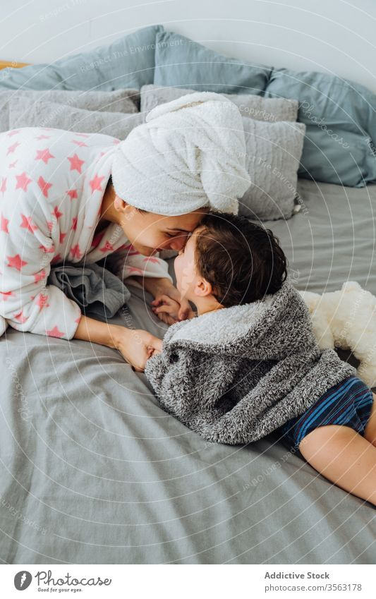 Mother playing with son in bedroom mother having fun bathrobe content game pastime little boy parent parenthood mom motherhood childhood kid adorable cute lying