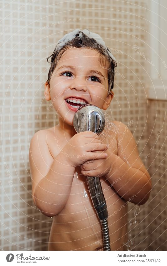 Cute boy singing in shower at home bathroom little foam smile child cute having fun kid cheerful content delight positive glad happy hygiene wet hair wash