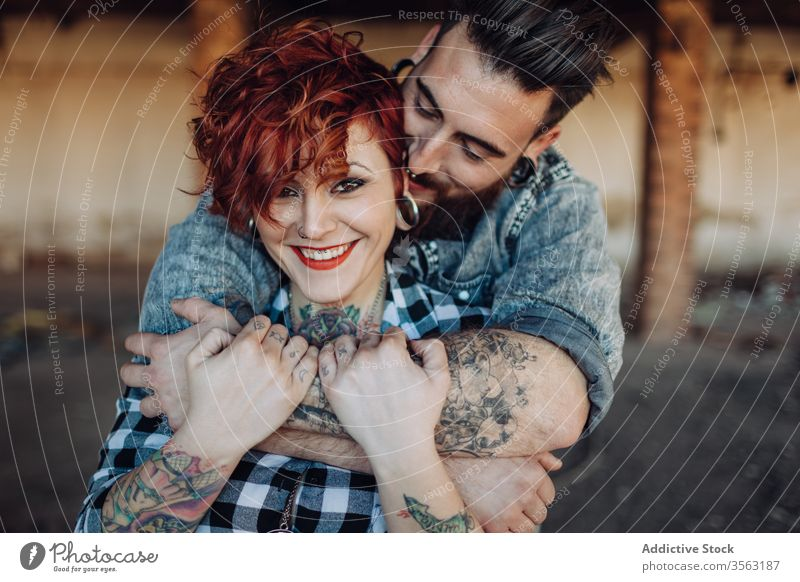 Happy young couple embracing near weathered building love embrace happy hipster street shabby together hug relationship tattoo boyfriend girlfriend affection