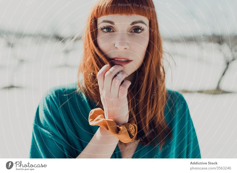 Sensual woman with red hair looking at camera style trendy sensual redhead young nature snow attractive female ginger fashion modern charming elegant makeup