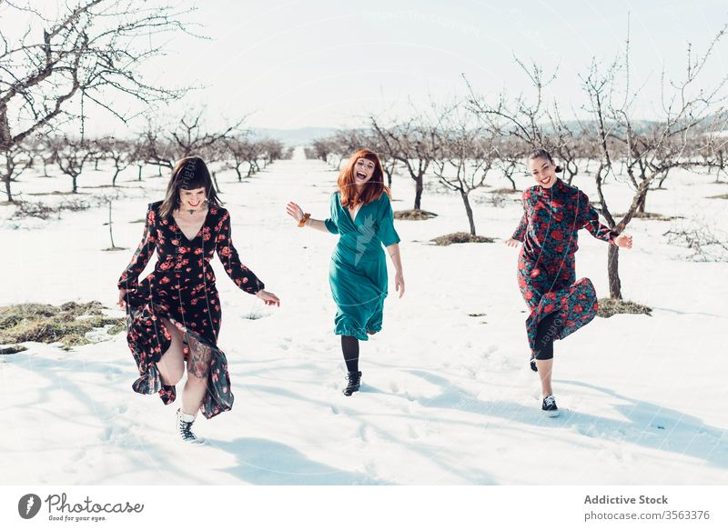 Happy fashionable women running on snow together happy fun winter field friend cheerful trendy nature style female young joy smile relax relationship laugh